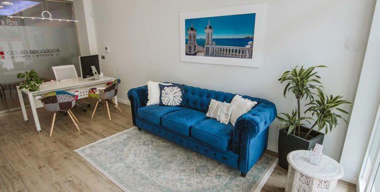 Sofá azul y zona de recepción Oficina Albir Abogado Inmobiliaria Costa Blanca