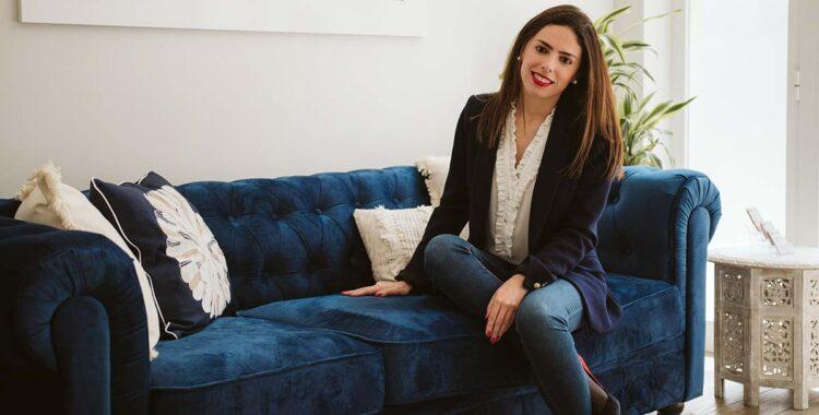Mujer sonriente en el sofá azul de asesoramiento jurídico-financiero de Empresas en España